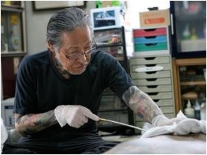 Le maître Horiyoshi durant une séance de tatouage