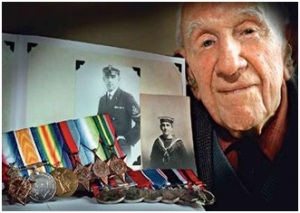William Evan Allan on his 100th bithday poses with the service medals he won in both world wars and with pictures of him as a young sailor and petty officer.